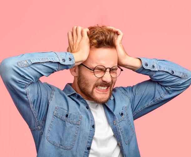Foto de um homem ruivo com as mãos na cabeça. Sua expressão é de dor